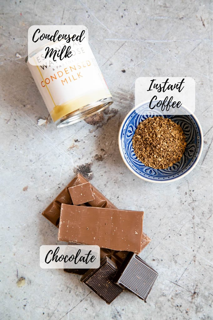 Condensed milk, instant coffee and dark and milk chocolate: the ingredients for chocolate coffee fudge. A photo from above with labels annotating each of the three items.