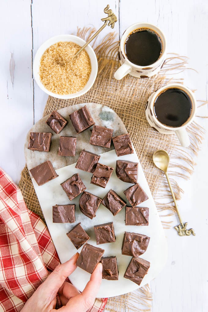 A top down picture of coffee fudge. You can see a hand picking up one piece. The fudge is on a marble board, itself on a piece of rustic hessian cloth.