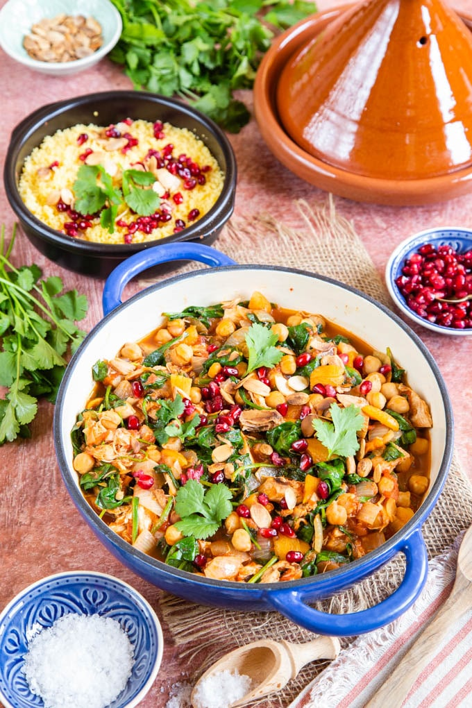 A shallow blue casserole dish of chicken tagine, garnished with fresh coriander leaves and pomegranate seeds. A dish of couscous and more pomegranate in the background, along with a brown tagine.