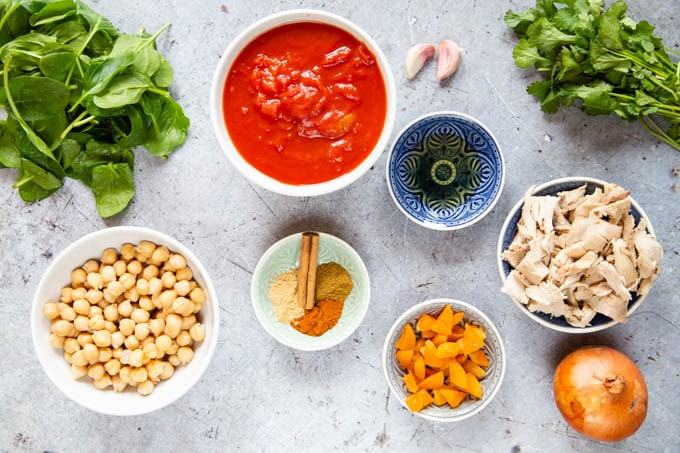 Ingredients for leftover chicken tagine, laid out in a mise en place. Chicken, chickpeas, apricots, spices, tomato, oil, onion, garlic, spinach and coriander leaves.