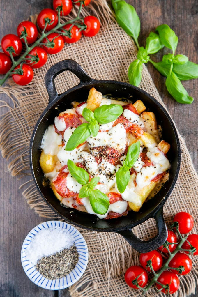 A top down picture of pizza fries in a small round cast iron skillet, surrounded by cherry tomatoes on the vine, basil leaves, and a pinch pot of salt and pepper.