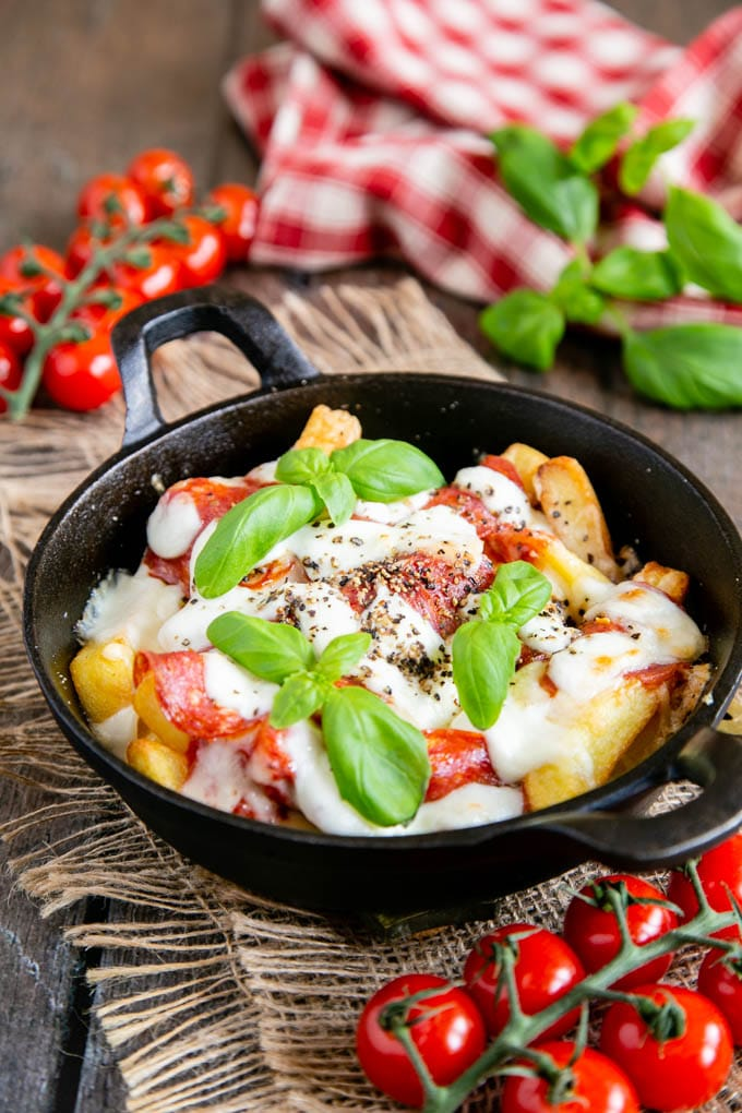 A small cast iron skillet of pizza fries, garnished with basil leaves. The dish sits on a hessian cloth