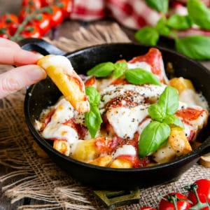 Close up of a hand removing one chip from a serving of pizza fries that's been garnished with basil leaves. Cherry tomatoes on the vine are in the background.