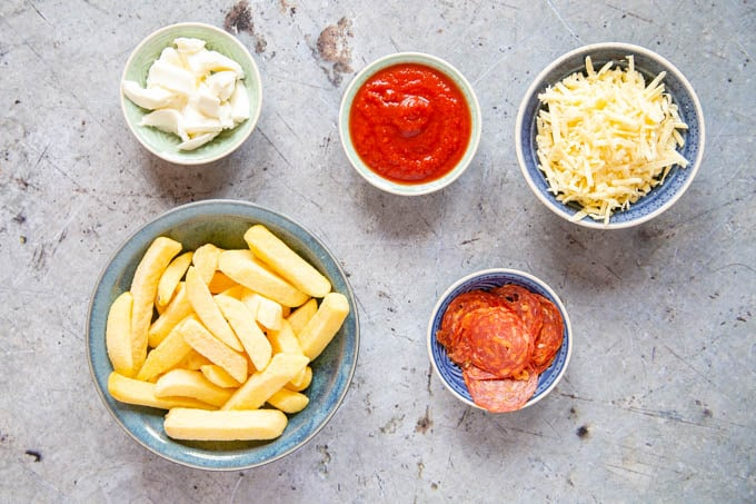 A top down picture of the ingredients for pizza fries - thick cut oven fries, pizza sauce, grated cheddar, mozzarella and sliced salami.