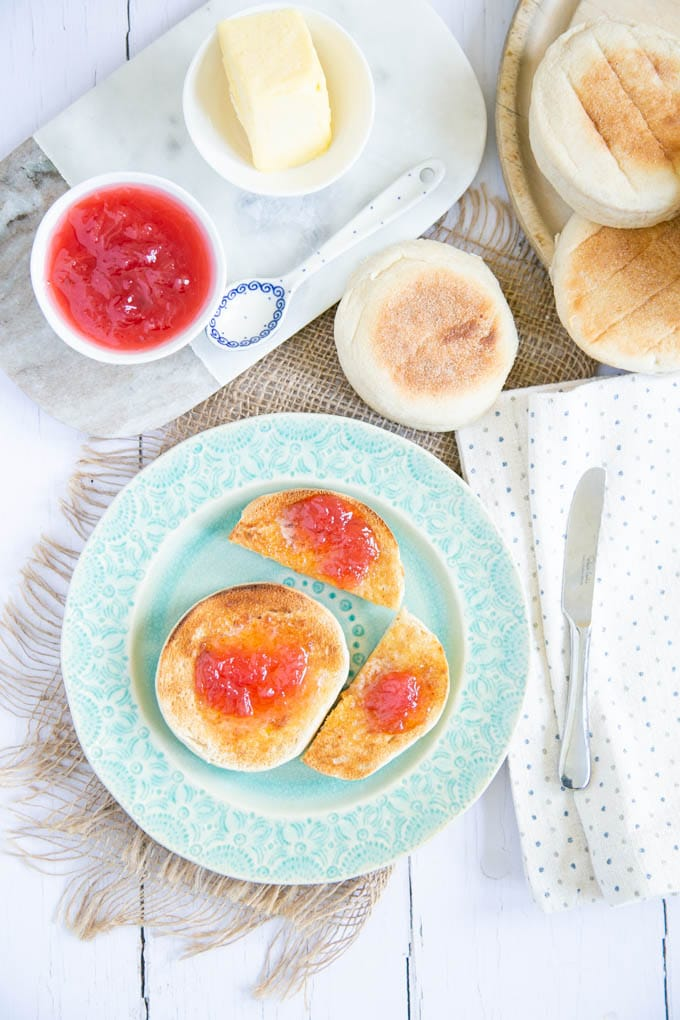 A top down picture of muffins spread with rhubarb jam and butter. Small bowls of jam and butter sit next to the plate.