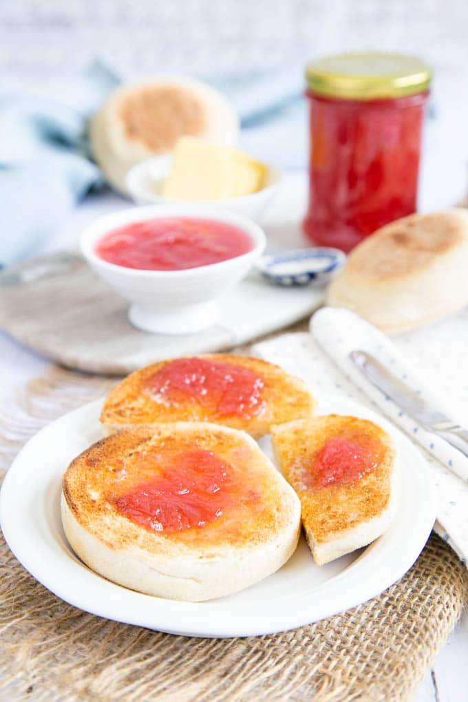 Toasted English muffins spread with butter and rhubarb jam. More jam is in the background, in a small bowl and also an unopened pot.