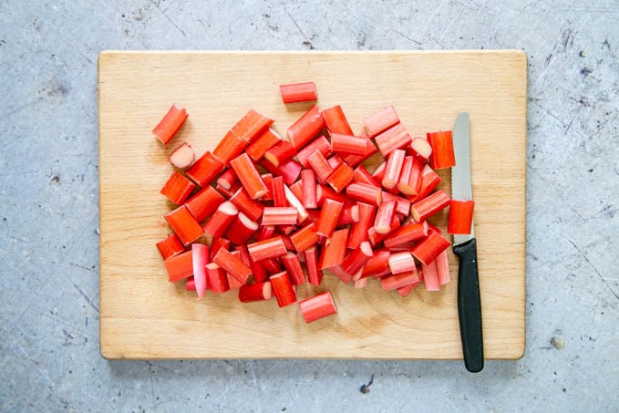"Rhubarb that has been cut into 1"" - 2.5cm pieces, on a wooden board."