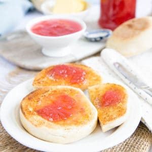 Two toasted English muffins, one cut in two, spread with butter and rhubarb jam, on a plate.
