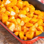 Close up of roasted butternut squash in a roasting pan.
