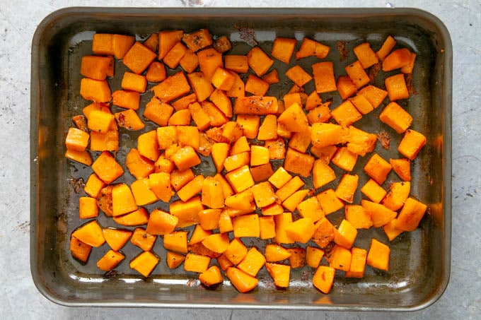 Cooked butternut squash in a roasting tray, from above.