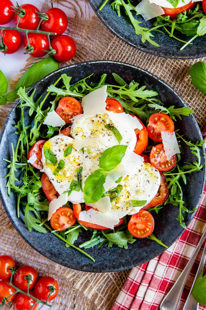 A top down picture of tomato and marinated mozzarella salad, in a mottled dark grey bowl on a rustic hessian cloth.