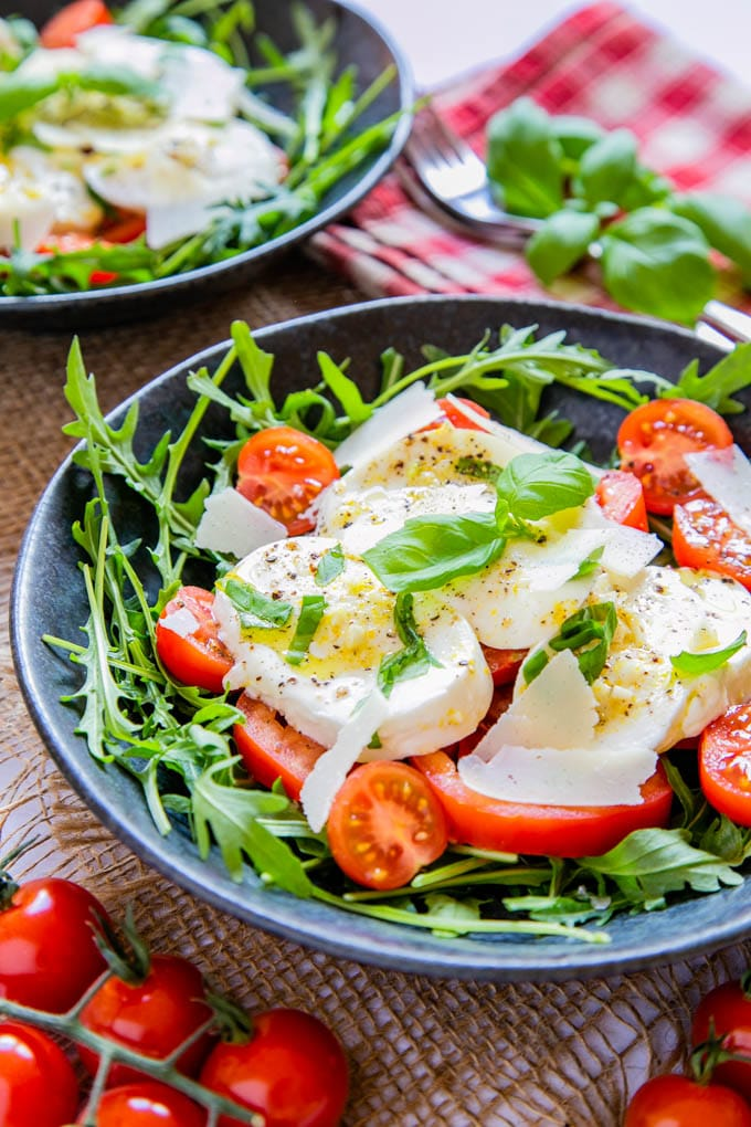 A tomato and mozzarella salad with rocket leaves, served on a dark grey plate.