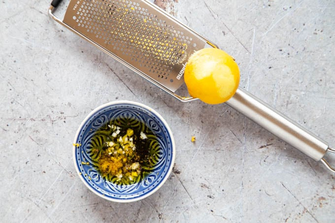 A picture of a half zested lemon on a grater, next to a small bowl