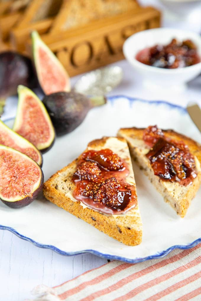 Two pieces of fig jam on toast on a plate, with halves of fig next to them. More jam in a small bowl out of focus in the background.