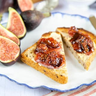 A close up of two pieces of toast spread with butter and fig jam