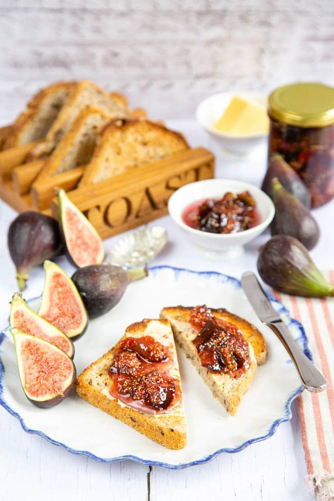 Two half slices of toast, spread with butter and fig jam, on a white plate with a blue rim. More jam in the background.