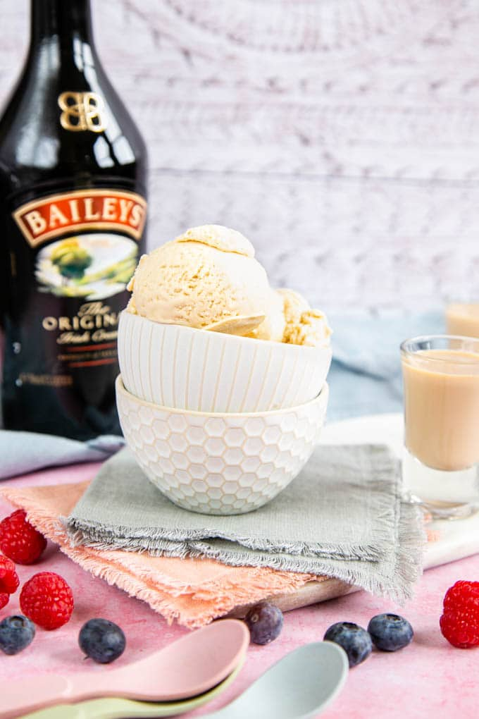 A small bowl of Irish cream ice cream, on a stack of pastel coloured cloths. A bottle of Irish cream is in the background.