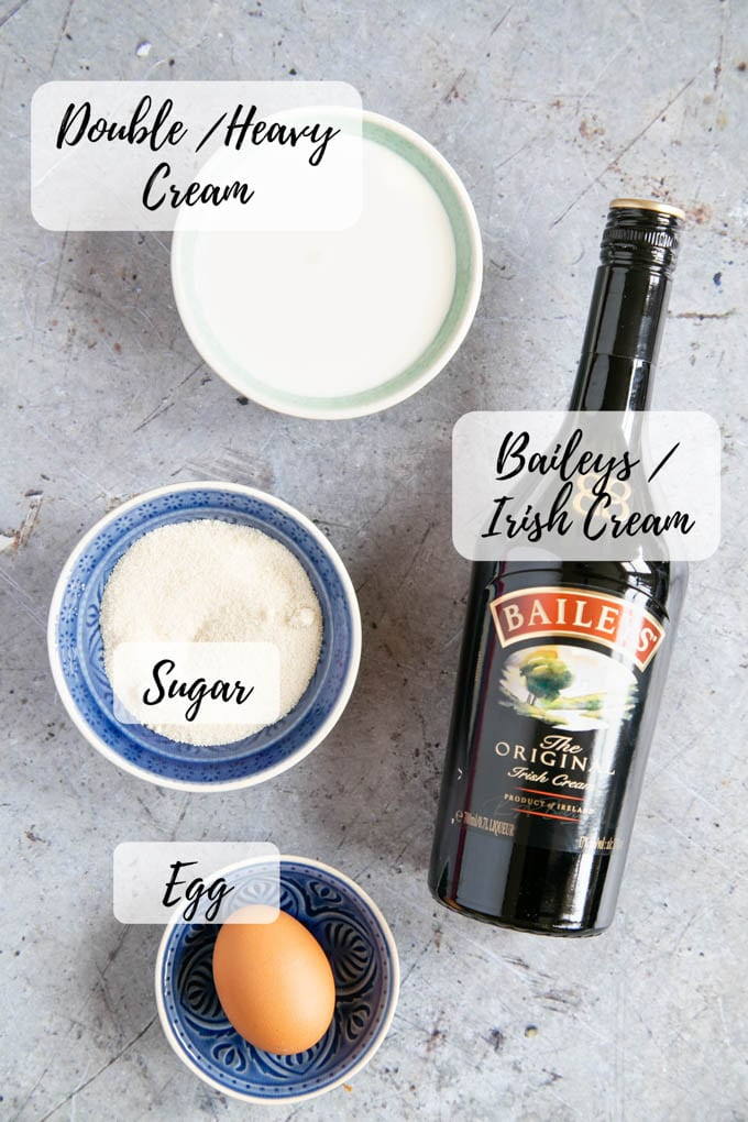 An annotated picture of the ingredients for Irish cream ice cream - double cream, sugar, Irish cream, and an egg.
