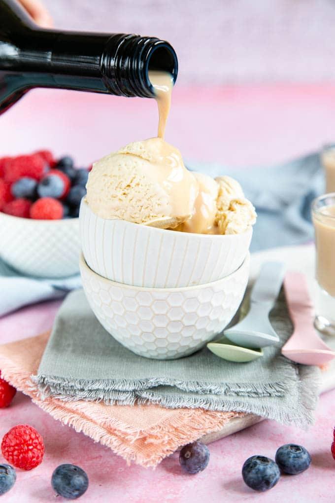 Pouring Irish cream onto a bowl of ice cream as an extra treat.