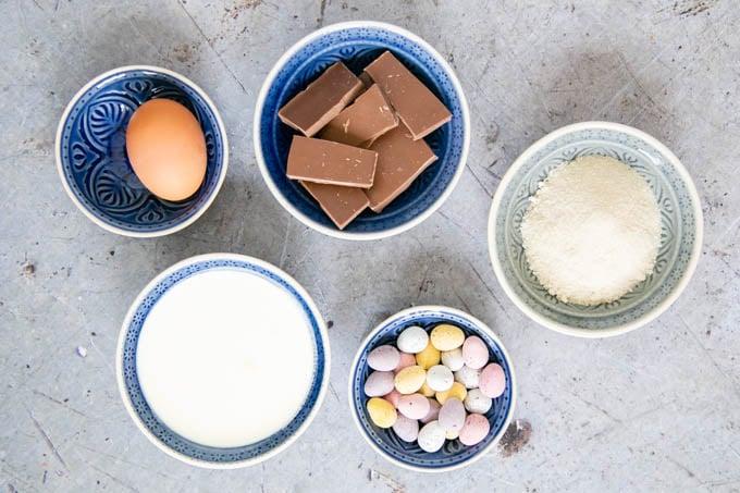 Ingredients for Easter mini egg ice cream - an egg, chocolate, sugar, cream, mini Easter eggs.