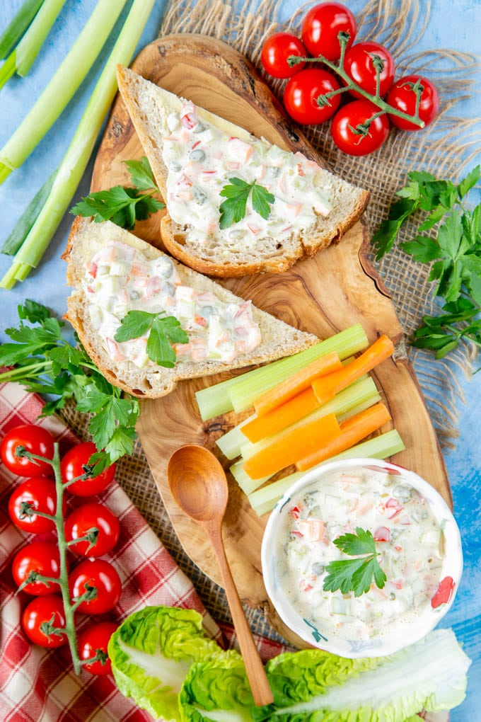 A table set with a wooden board with slices of bread spread with sandwich spread surrounded by salad vegetables