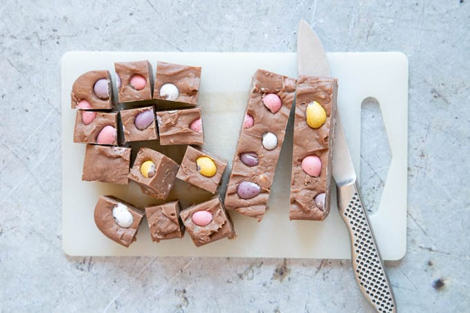 """Cutting the fudge into individual 1""""/2.5cm pieces, on a chopping board, with a sharp kitchen knife."""