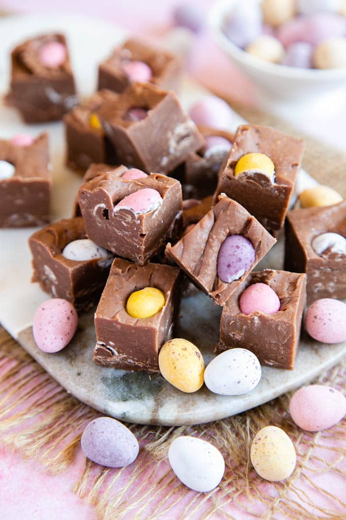 A close up of individual pieces of mini egg fudge, on a marble serving board.
