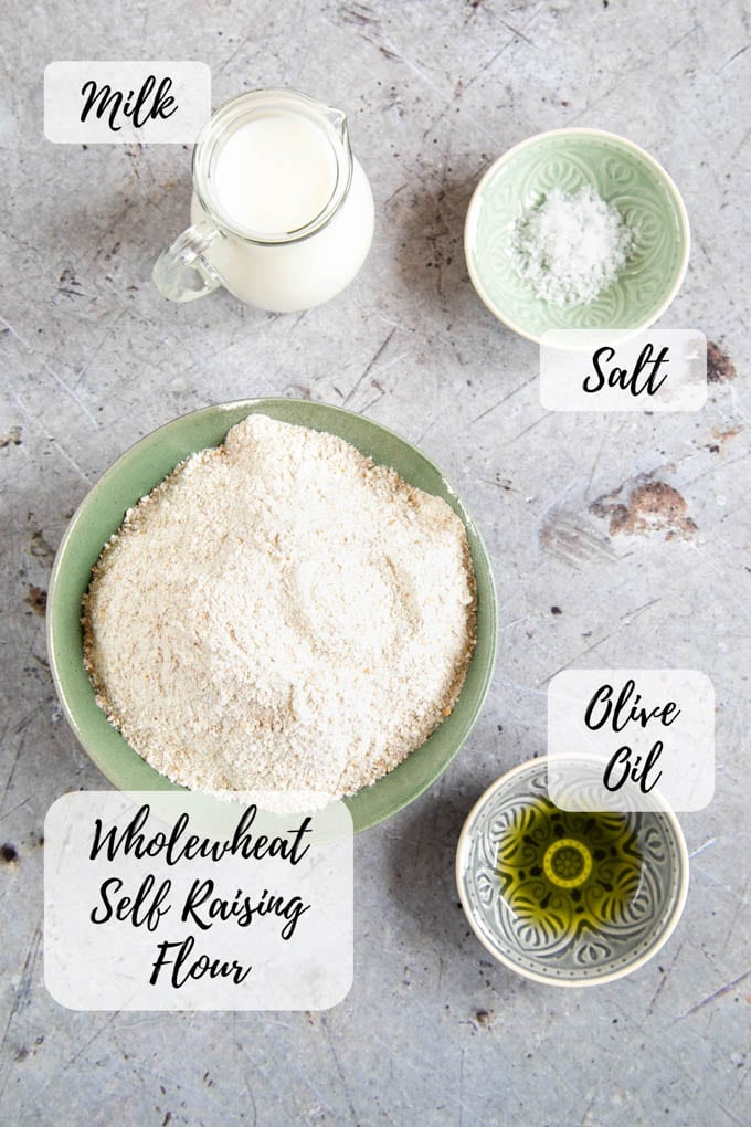 A top down picture of the ingredients for wholemeal self raising flour bread: flour, milk, salt, oil.