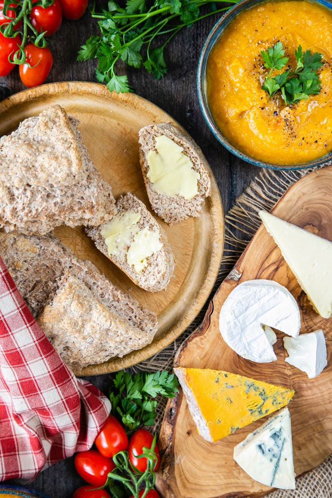 A top down picture of wholemeal bread from self raising flour, cut into wedge slices, buttered, on a board, With cheeses, bowls of soup and half a loaf.