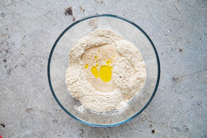 Liquid ingredients added to the flour and salt, in a glass bowl. Picture taken from above.