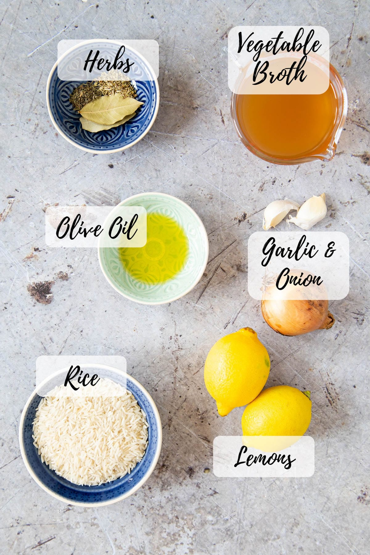 An annotated top down picture of ingredients for Greek rice: rice, garlic, onion, lemon, herbs, vegetable broth, and olive oil.