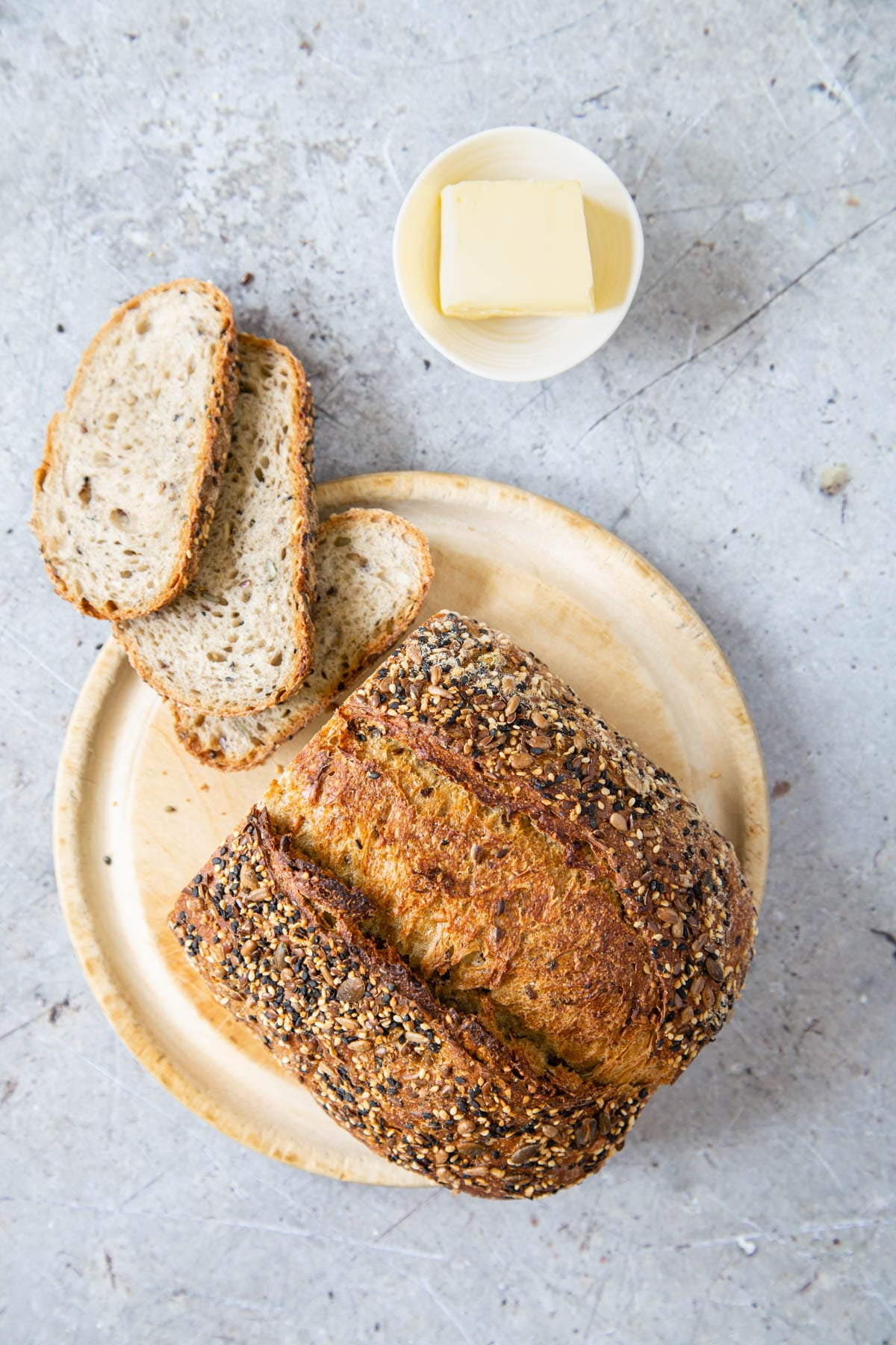 A good quality rustic loaf of bread, with some slices cut, sitting on a round breadboard. A small dish of butter sits next to the bread. Picture taken from above.