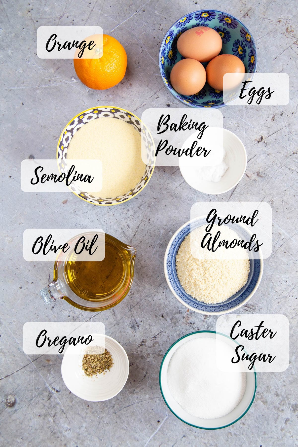 An annotated top down picture of the ingredients for orange olive oil cake: olive oil, eggs, an orange, oregano, sugar, ground almonds, baking powder, and semolina.