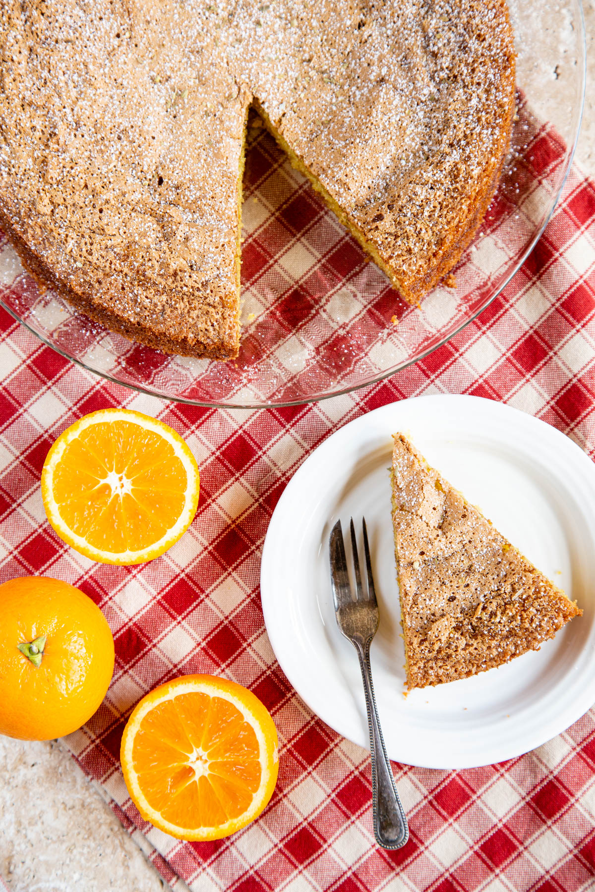 A top down picture of olive oil cake with a slice cut. The slice is on a sideplate, next to the cake. One whole and two half oranges sit next to the plate.