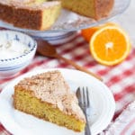 Close up of a slice of orange olive oil cake. Half an orange and the rest of the cake is out of focus in the background.