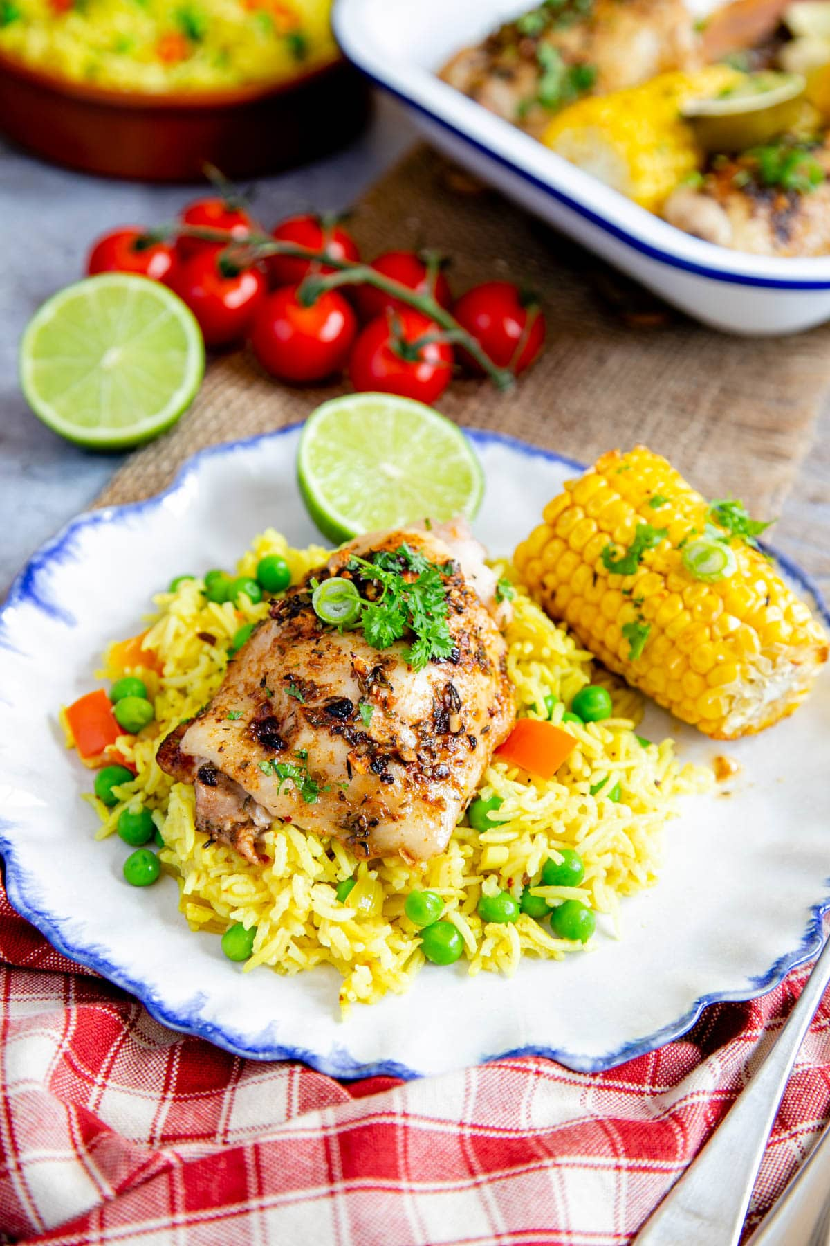 A plate of delicious peri peri chicken served on fragrant yellow rice. A half cob of corn sits on the blue rimmed plate. In the background are dishes holding more chicken and rice.