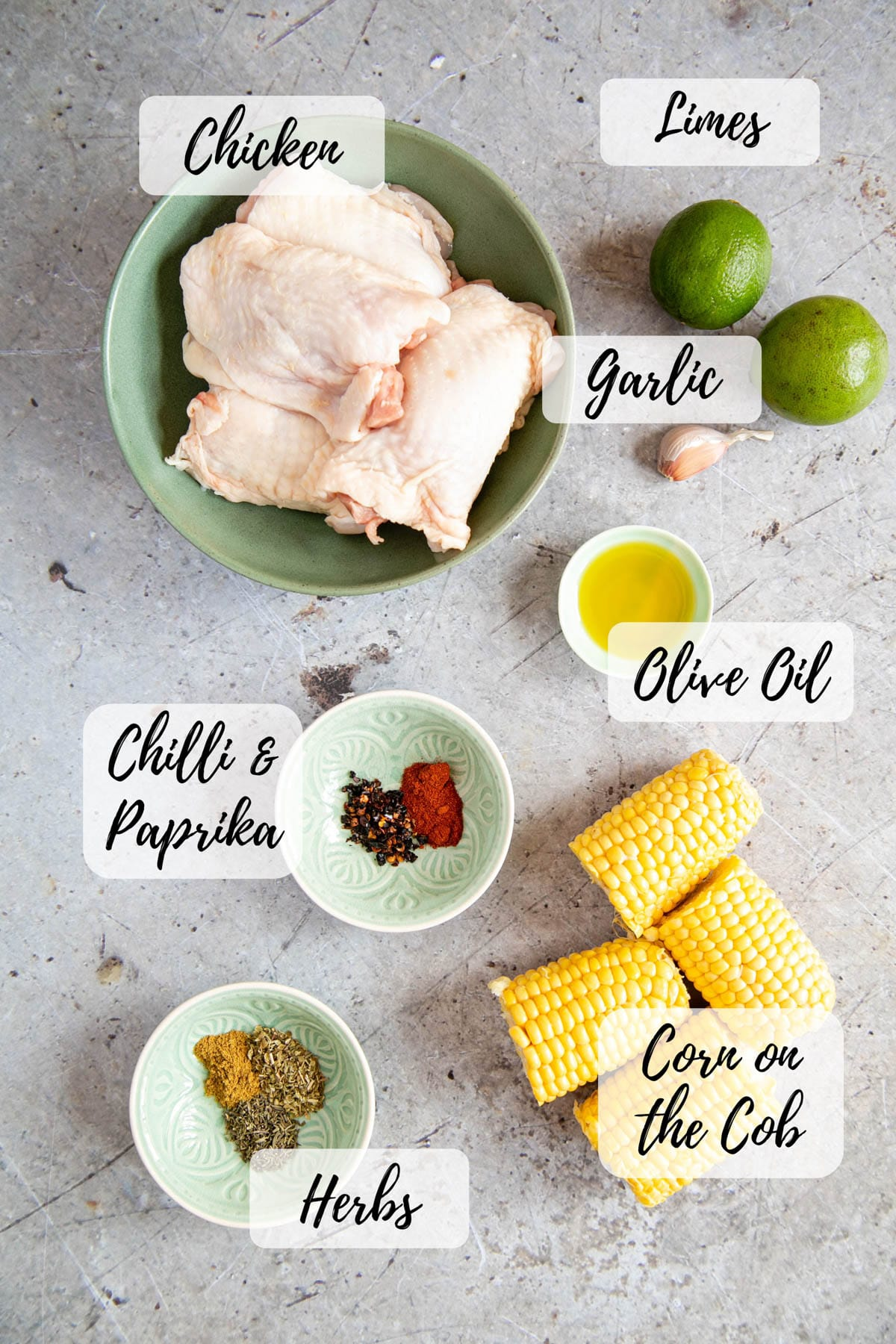 An annotated picture of the ingredients for peri peri chicken: chicken thighs, limes, garlic, olive oil, chilli flakes, paprika, corn on the cob, and herbs.