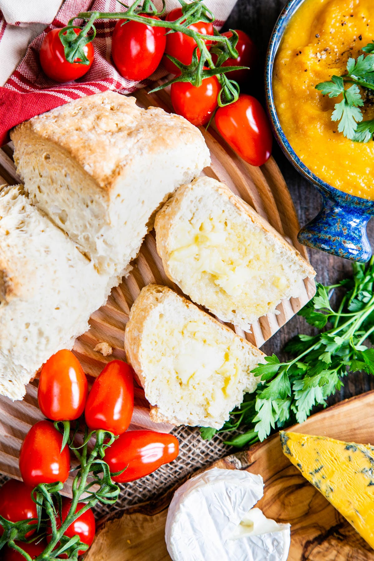 A top down picture of two wedges and half a loaf of self raising flour bread. The bread, on a board, is surrounded by tomatoes, 2 bowls of soup, and a couple of pieces of cheese.