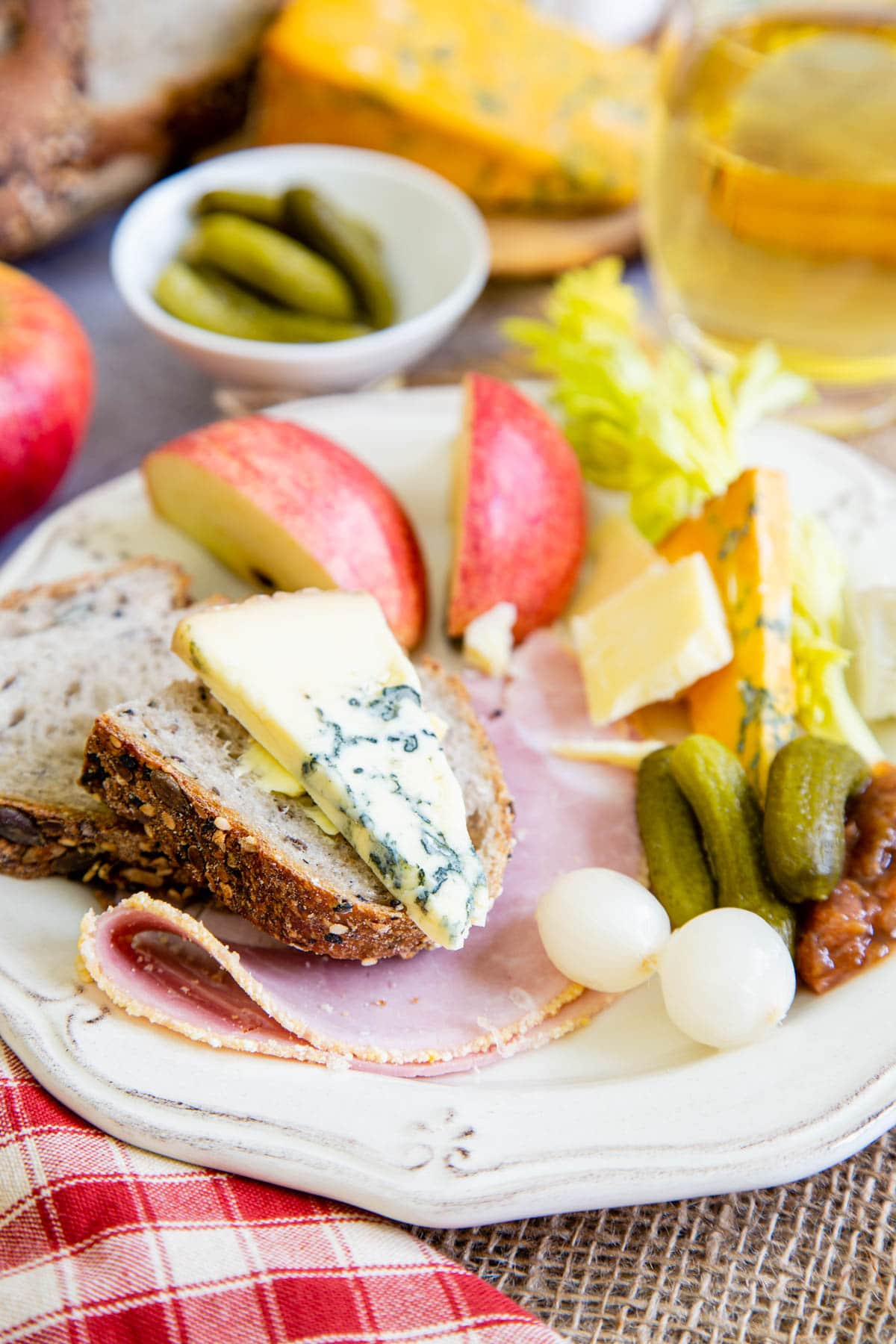 Close up of a slice of cheese on bread on a ploughmans lunch. Also on the plate are ham, garnishes, apples, celery, and more cheese.
