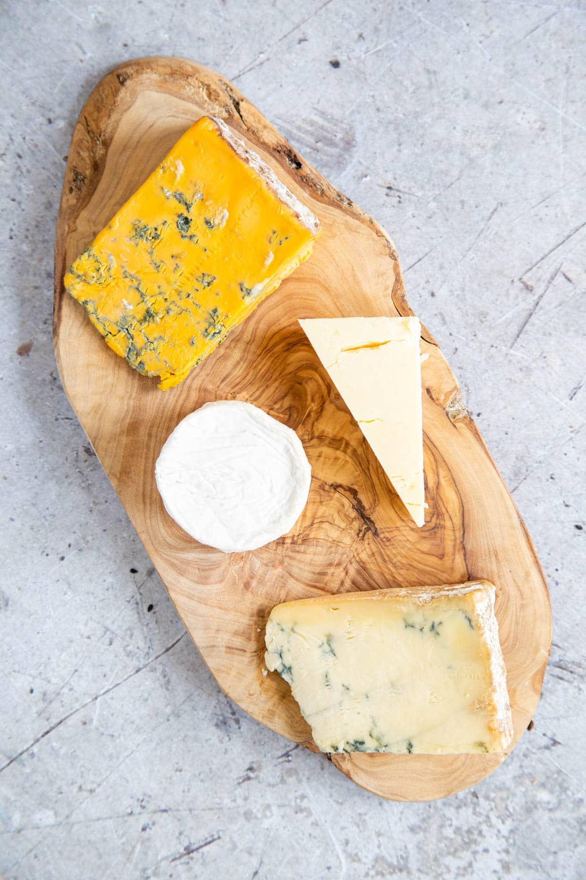 A selection of four cheeses - 2 blue, one plain and one goat's cheese, arranged on an olivewood board.