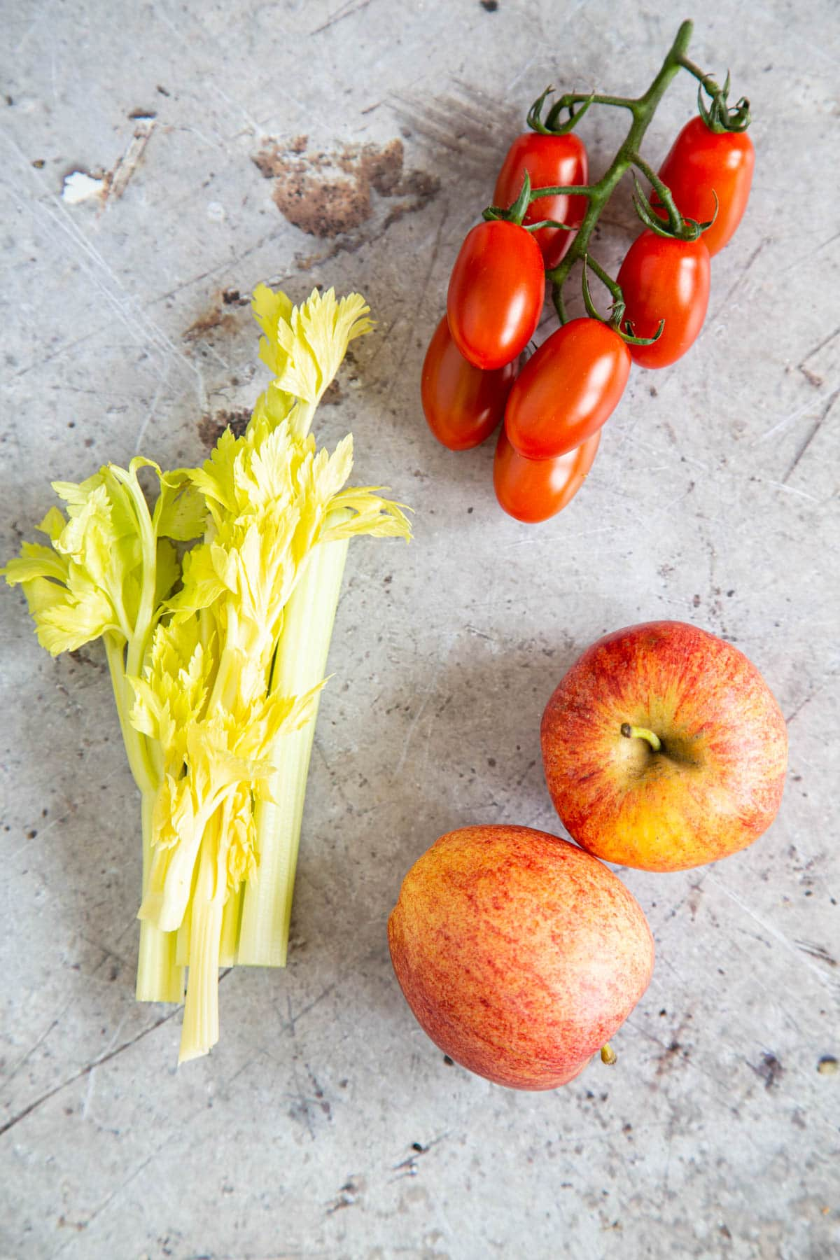 Two apples, some tomatoes on the vine, and some half sticks of celery, pictured from above.