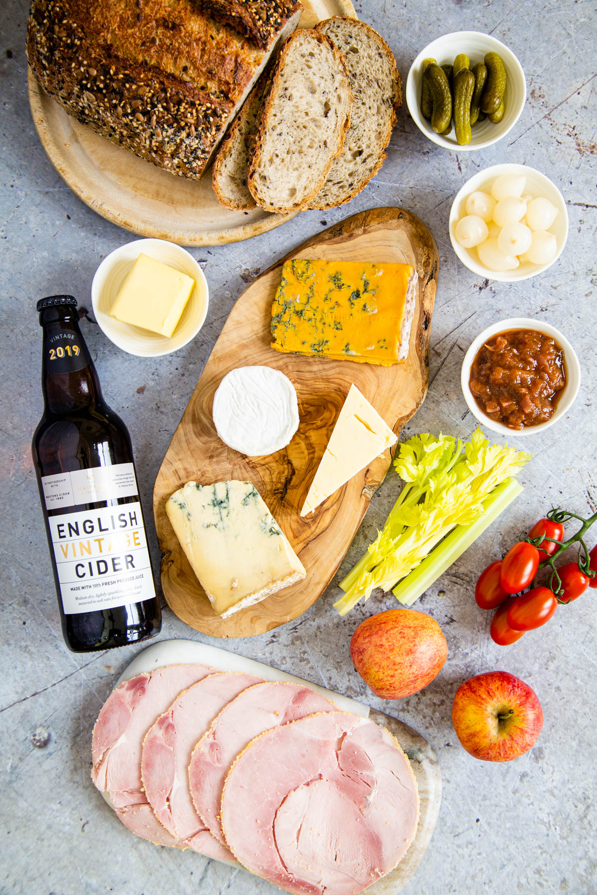 Ploughmans lunch - a selection of cheeses on a board and some sliced ham on a marble platter. A bottle of cider lies next ot the cheese. Sliced bread in the top of the picture.