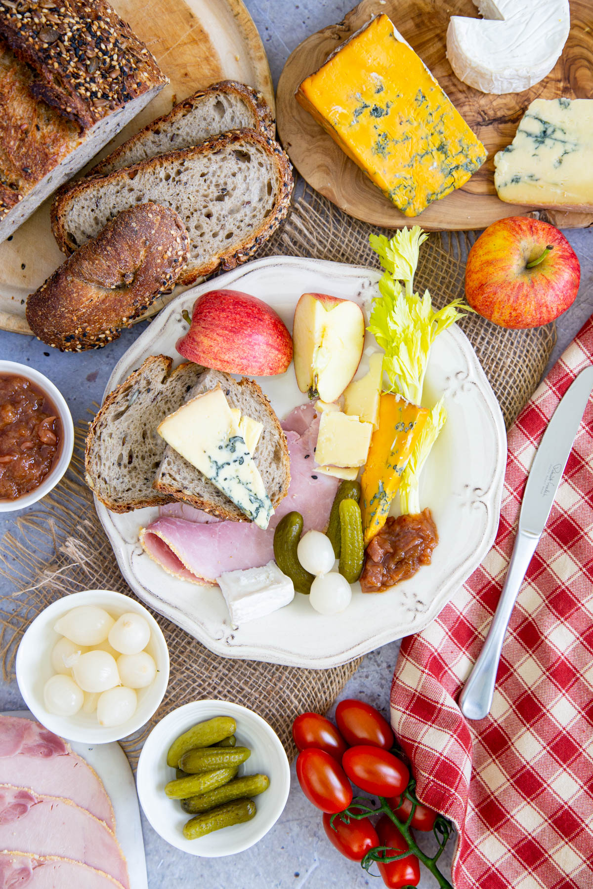 A top down picture of a hearty ploughmans lunch with bread, ham cheese, apples, celery and garnishes.