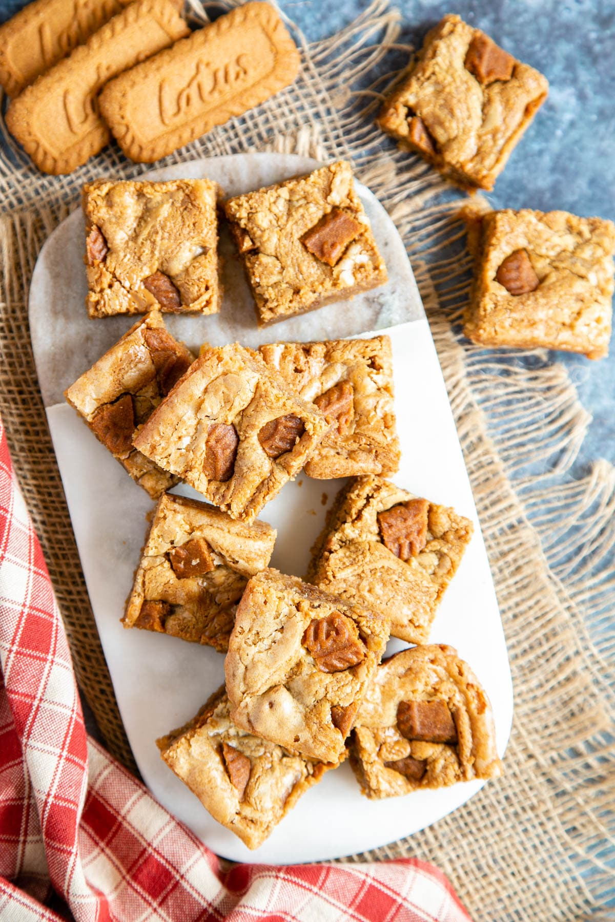 A top down picture of a marble board covered in biscoff blondies. Three lotus biscuits sit next to the board.