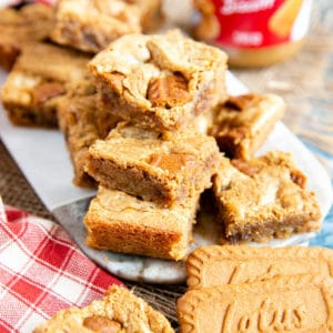 A stack of easy biscoff blondies on a marble board, with a jar of Biscoff spread out of focus in the background. Two Biscoff biscuits lean next to the board.