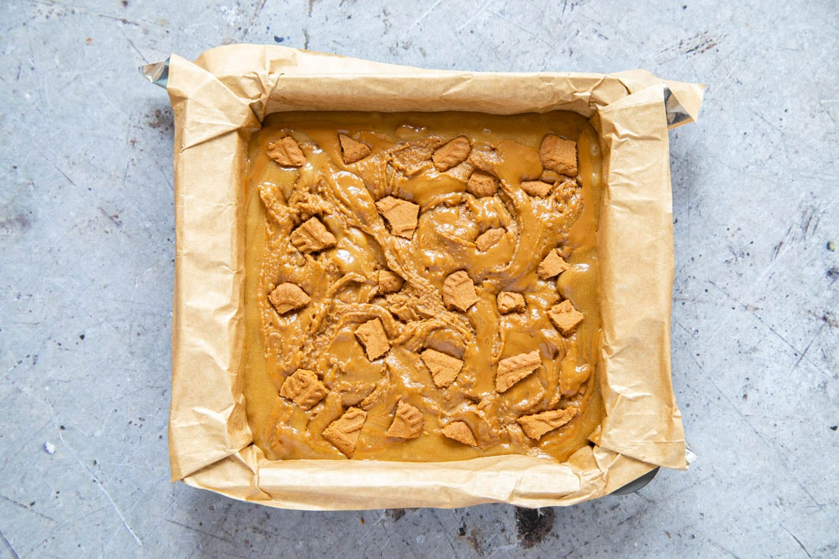 The blondies ready to cook. The top is covered with broken Lotus biscuits.