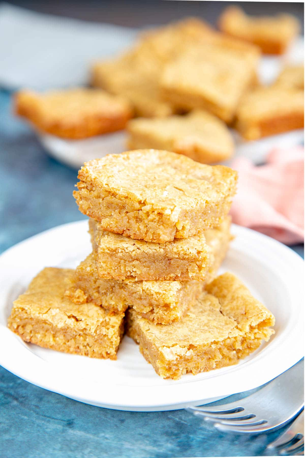 A stack of three blondies arranged on three more, all on a small sideplate. Two forks are half seen in the foreground, and more blondies in the background.
