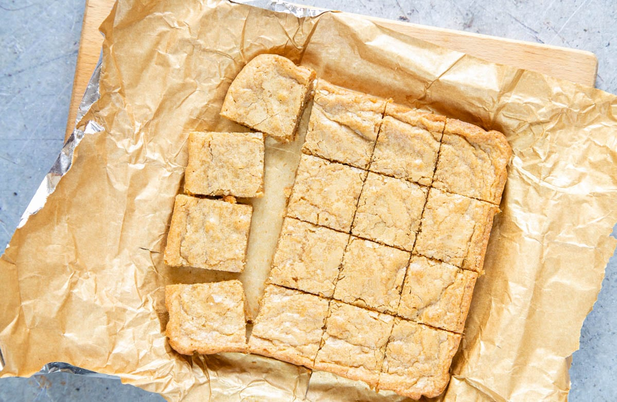 """A top down picture of a tray of cooked blondies being cut into squares. And 8""""x 8"""" tray (20cm x 20cm) makes 16 blondies."""