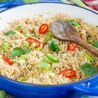 A close up of easy Chinese rice, ready to serve. The dish has been garnished with slices of red and green chilli and coriander leaves. A wooden spoon sits on top of the rice.