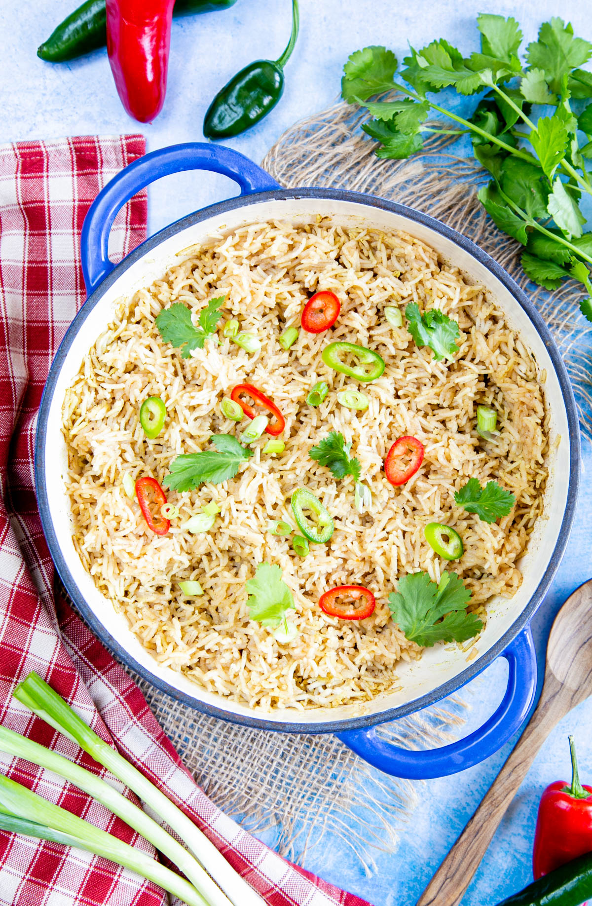 A top down picture of easy Chinese rice, garnished with coriander and slice of red and green chillies, in a shallow casserole dish. Surrounding the dish are more chillies and fresh coriander, Spring onions, a small wooden spoon and a checked cloth.